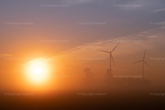 Windkraftanlagen im morgendlichen Nebel | Aufgehende Sonne mit Frühnebel und Windkraftanlagen im Hintergrund.