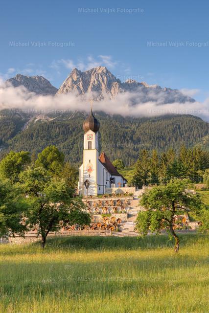 Morgens in Grainau in Bayern | Blick zur Pfarrkirche St. Johannes der Täufer in Obergrainau, vor der mächtigen Kulisse des Wettersteingebirges mit der Alpspitze links hinter den Wolken, dem Großen Waxenstein in der Bildmitte und der Zugspitze rechts im Hintergrund.