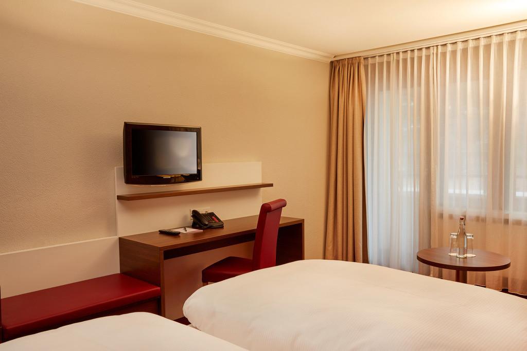 zimmer-superior-doppelzimmer-bett-fernseher-01-hplus-hotel-engelberg