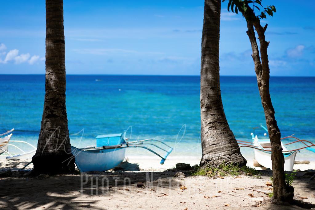 Eine herrliche Strandszene   Idyllischer Strand mit einem typischen blauen Boot auf den Philippinen