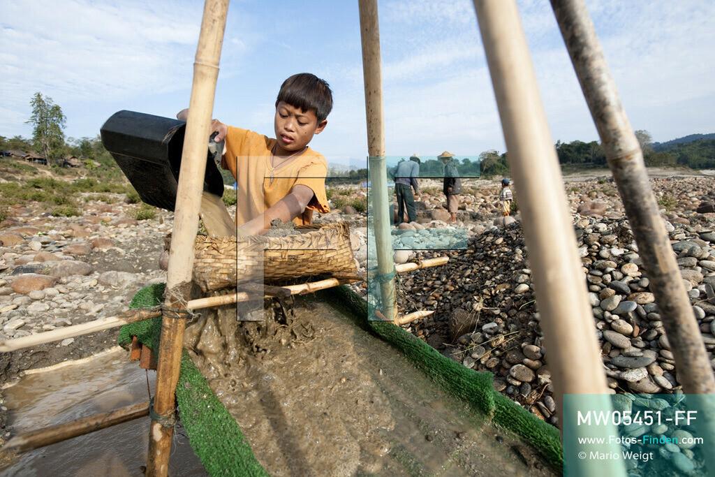 MW05451-FF | Myanmar | Kachin State | Myitson | Adee spült den Flusssand über die Holzrutsche und hofft, dass winzige Goldpartikel in der grünen Matte zurückbleiben. Der 13-jährige Maung Adee lebt mit seiner Tante und seinem Onkel im Dorf Thanphe, drei Kilometer vom Zusammenfluss des Ayeyarwady. Dort schürft Adee mit seiner Familie nach Gold.  ** Feindaten bitte anfragen bei Mario Weigt Photography, info@asia-stories.com **