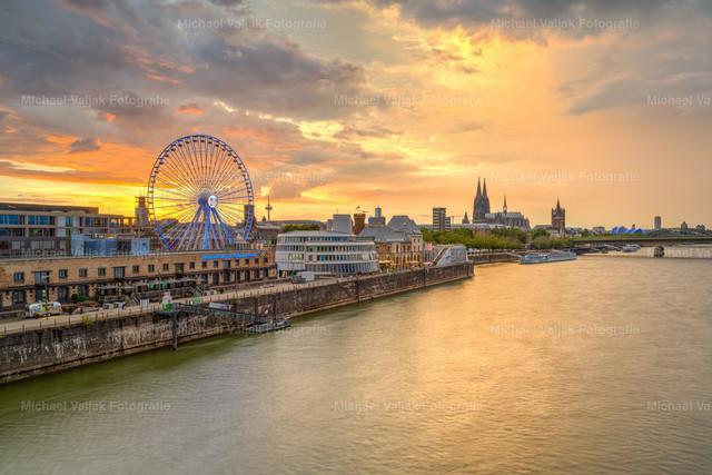Skyline von Köln mit Riesenrad | Die Skyline von Köln am Abend bei einem aufziehenden Gewitter. Gerade noch rechtzeitig kommt die Sonne durch und bringt die Wolken zum Glühen.