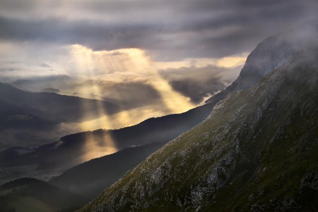 Magische Sonnenstrahlen | Das Gebirge hat immer eine Überraschung parat. Im Baskenland im Norden Spaniens zeigt sich das Wetter von seiner wechselhaften Seite. Dramatisch bricht die Wolkendecke für einige Minuten auf und die Sonnenstrahlen treffen auf die hügelige Landschaft. Fantasy pur.