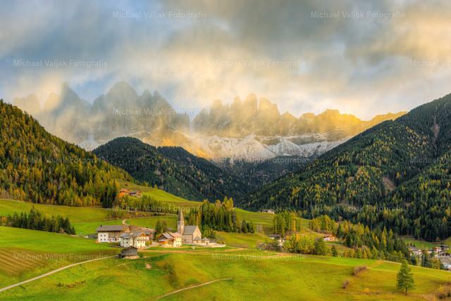 St. Magdalena im Villnösstal in Südtirol   Wetterumschwung im Villnösstal, die Geislerspitzen schauen durch die sich auflösenden Wolken hindurch, welche durch die untergehende Sonne angeleuchtet werden.