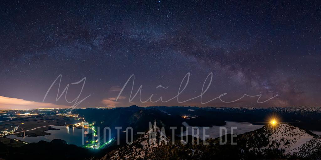 Der Milchstraßenbogen im Winter | Eine sternenklare Nacht in den bayerischen Voralpen. Die Milchstraße zieht sich über das Gipfelkreuz