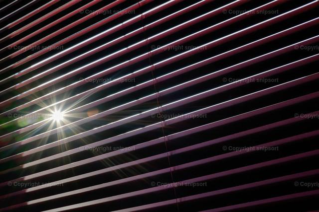 Zugezogene Jalousie | Sonne schimmert durch die geschlossenen Lamellen von roten Jalousien